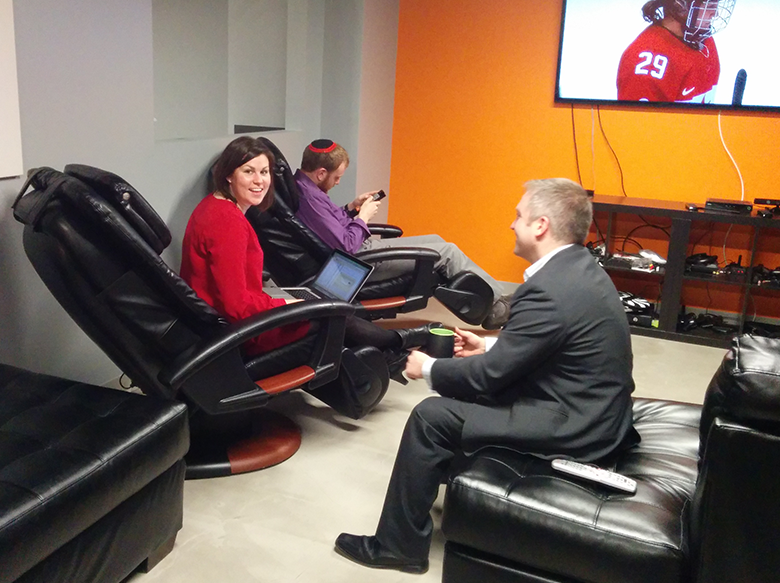 Uber Offices members talk while relaxing in the massage chairs.